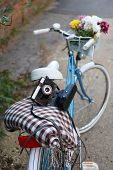 Old bicycle with flowers in metal basket, camera and checkered blanket closeup