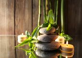 Spa stones, candles and bamboo branches on mirror surface on wooden wall background