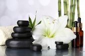 Spa composition with orchid and spa stones on table on light background