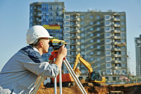 image of geodesic  - Surveyor builder worker with theodolite transit equipment at construction site outdoors during surveying work - JPG