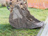 Closeup Of Muddy Excavator Shovel On Grass Near Construction Area