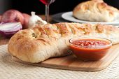 stock photo of cheese platter  - Homemade stromboli or stuffed bread with broccoli potatoes garlic onions and mozzarella cheese along with a side of marinara dipping sauce - JPG