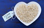 Plate Of Nutritious And Healthy Oat Flakes In Heart Shaped Bowl On Dark Blue Rustic Wood Table, With