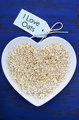 image of oats  - Plate of nutritious and healthy oat flakes in heart shaped bowl on dark blue rustic wood table with I Love Oats message tag vertical - JPG