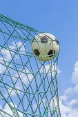 Football caught in goal net with blue sky