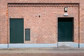Old brick wall with green doors and street
