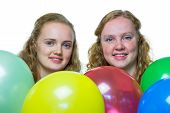 Two girls behind various colored balloons