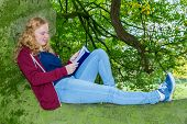 Girl lying reading book in green tree