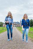 Two girls walking on road away from castle