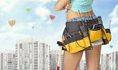 Woman in tool belt standing backwards. Cropped image. High-rise buildings as backdrop