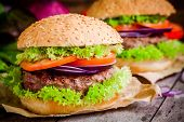 Two Homemade Hamburgers With Fresh Green Lettuce, Tomatoes And Red Onions