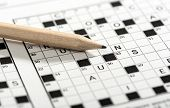 image of puzzle  - Conceptual Sharpened Pencil on Top of Crossword Puzzle Game Paper in Close up Shot - JPG