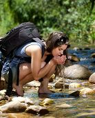 Hiking Woman Drinking Water With Hands From Stream