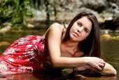 Young Woman In Red Dress Sitting In River Water In Summer