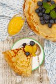 Crepes With Blueberries, Lemon And Mint Sauce And A Cup Of Tea Top View