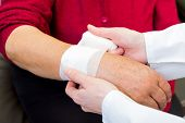 pic of bandage  - Photo of doctor bandaging the elderly woman wrist - JPG