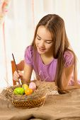 Portrait Of Cute Smiling Girl Preparing Easter Eggs