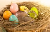 Closeup Shot Of Colorful Easter Eggs And Glass Rabbit Lying In Nest