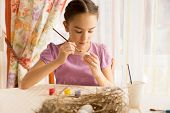 Girl Sitting On Kitchen And Painting Easter Egg