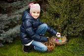 Girl Finding Easter Eggs On Lawn At Backyard