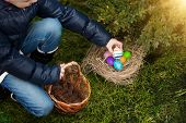 Closeup Shot Of Little Girl Putting Painted Egg In Basket