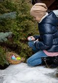 Girl Kneeling Next To Tree And Picking Easter Egg