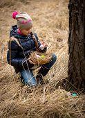Girl Having Easter Egg Hunt At Forest
