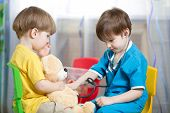 kids play doctor with plush toy