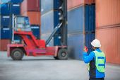picture of loading dock  - foreman control forklift handling the container box load to big truck - JPG