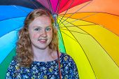 Teenage girl under colored umbrella