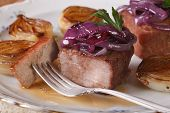 Meat With White And Red Caramelized Onions On A Plate