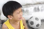 stock photo of crying boy  - Young boy cry and tear during play football in front of concrete wall of concrete wall - JPG