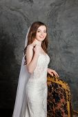 Photo of a beautiful happy bride in luxurious wedding dress into elegant expensive interior