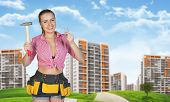 Woman in tool belt holding hammer and hails, smiling. Green hills, road, buildings as backdrop