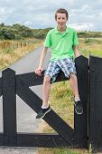 Teenage boy sitting on black wooden fence in nature