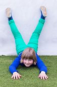 Young girl lying upside down against wall