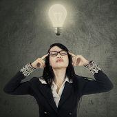 Female Worker Thinking Under Bright Lamp