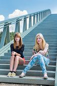 Two teenage girls sitting on metal bridge