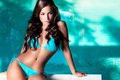 image of swimsuit model  - beautiful long hair woman in blue bikinil posing by the pool outdoor portrait - JPG