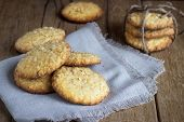 stock photo of chocolate-chip  - oatmeal cookies on white linen napkin on wooden table - JPG