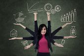 picture of multitasking  - Multitasking businesswoman with eight hands holding priority things - JPG