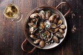 foto of clam  - Shells vongole venus clams in copper cooking dish and wine on dark wooden background - JPG