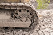 pic of caterpillar  - Mudstained Caterpillar tracks of a yellow earth moving digger at rest - JPG