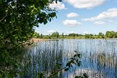 picture of bent over  - White clouds on the blue sky over blue lake with reflections - JPG