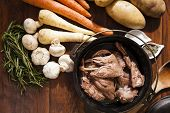 stock photo of rutabaga  - Cast iron pot of bottled rabbit with vegetables laid our around the pot - JPG