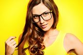 pic of spectacles  - Beauty portrait of a happy young woman in spectacles and bright yellow dress over yellow background - JPG