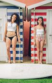 stock photo of beach hut  - Portrait of beautiful surfer women couple with bikini and surfboard standing over a beach striped huts background - JPG