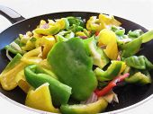 picture of yellow-pepper  - Green yellow peppers and onions chopped in the cooking pan on white background - JPG