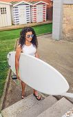 picture of board-walk  - Portrait of curly brunette surfer woman with white top and sunglasses walking with a surfboard - JPG