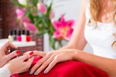 pic of beauty parlor  - Woman receiving manicure in beauty parlor - JPG
